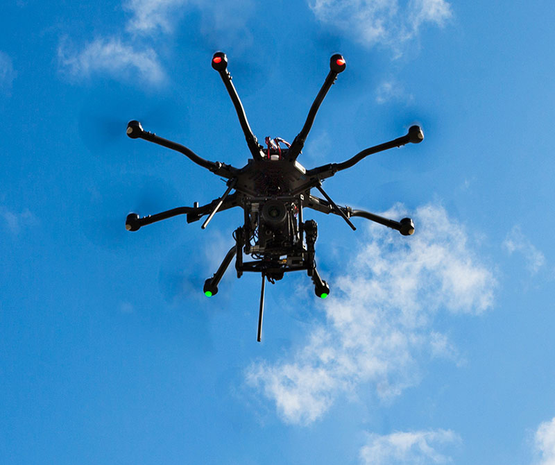 große Drohne im Flug vor blauem Himmel mit Alexa-Mini oder Red Epic Kamera