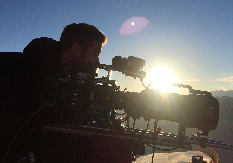 Kameramann mit Sony F55 Kamera und Canon 10-1000mm Optik im Gegenlicht bei Dreharbeiten in den Alpen